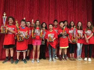 Group of sixth-grade music students in red shirts holding large trophies
