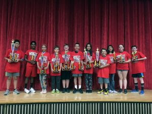 Gr. 7 musicians onstage, holding trophies