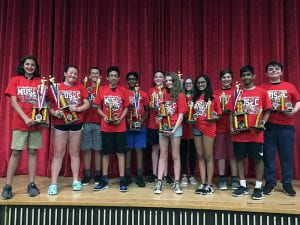Gr. 8 musicians onstage, holding trophies