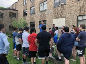 Farmer speaking with students in courtyard