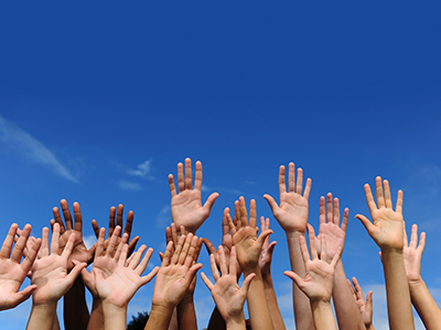 Cluster of hands raised against blue sky