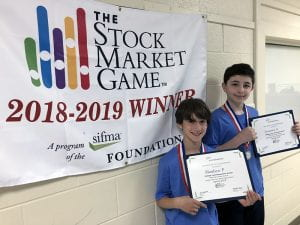 Two students with certificates and Stock Market Game banner