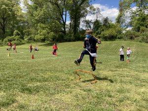 WOS student jumping hurdle at Field Day