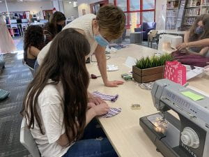 Teacher assists student with sewing project