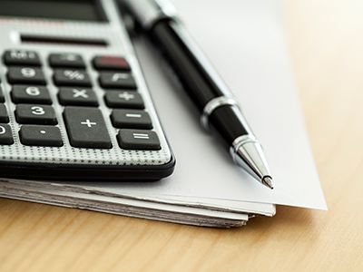 Closeup of calculator and pen on a pile of papers on a wood surface