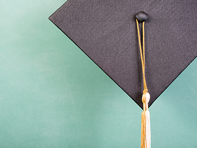 Closeup of grad mortarboard with gold and white tassel on green chalkboard background
