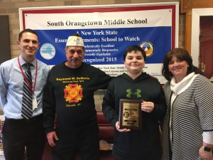 Seventh-grader Anthony D. holding plaque with VFW Commander in Chief Antonucci, Principal Tesik and Assistant Principal Corey