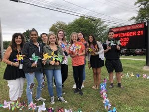TZHS artists with teacher holding Pinwheels for Peace on lawn