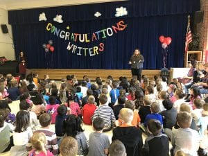 """Congratulations Writers"" banner in cafeteria with students seated"
