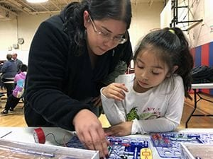 Mom helping young daughter with circuits project