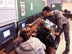 Khader Humied offers pointers to SOMS eighth-grade technology class