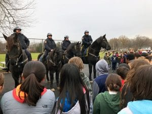 Four mounted police officers face a crowd of students for outdoor lesson