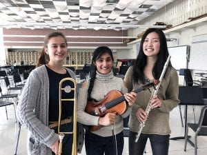 Three female musicians holding instruments