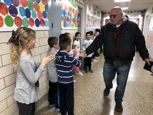Bus driver high-fives students in hallway