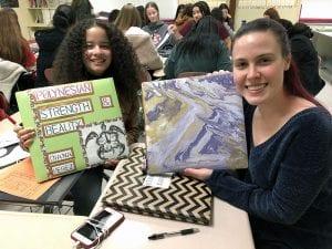Two female students holding Senior Portfolio scrapbooks