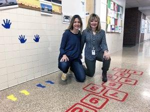 Two teachers crouching in sensory hallway