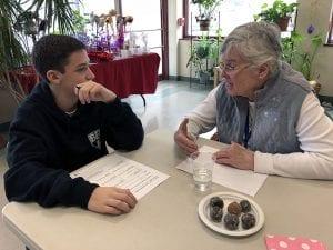 Student listening to senior citizen talking at table