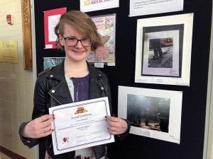 Student artist with certificate and photograph