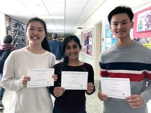 Three students standing with certificates