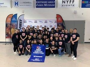 Robotics team with winners banner