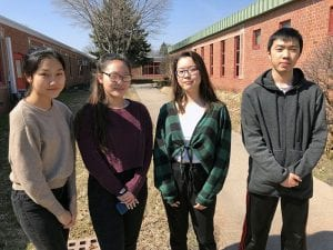 Four students standing in courtyard