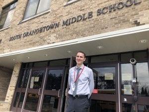Dr. Corey standing in front of school