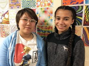 Two student artists with artwork in background