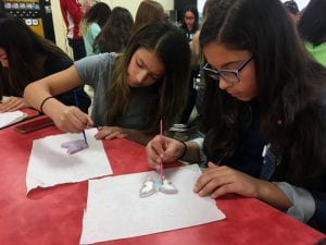 Two female students painting ceramic butterflies