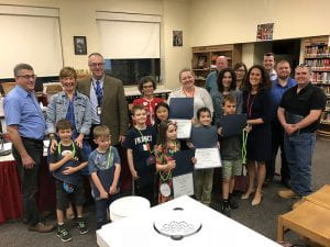 Elementary school students with teachers, administrators and Board members posed in library