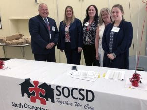 HR staffers standing by table covered with SOCSD tablecloth