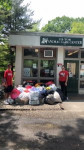 A male and a female student with bags of donations outside animal shelter