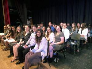 Large group of high school seniors, seated on stage
