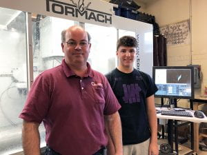 SO BOTZ mentor Joey Gottlieb with freshman Giovanni L. standing in front of CNC mill
