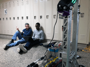 Male mentor sitting on floor with student with robot in foreground