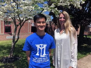 Student standing under flowering tree with principal