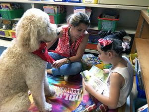 Young girl reading to attentive white poodle and owner
