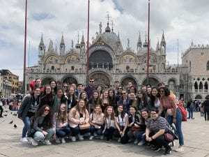 Group of students posed in St. Marks Square, Venice with basilica in background