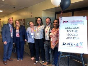 Welcome to the Job Fair sign with six administrators smiling
