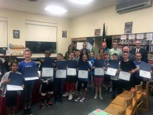 Group of students with certificates and district administrators