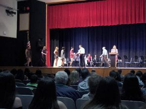 Line of students on stage receiving certificates from counselor