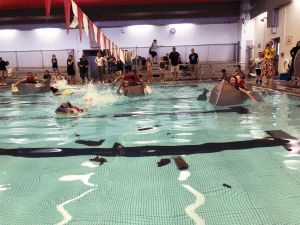 Students paddling across pool in cardboard boats