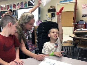 Student holding red rocket up in the air as teacher and classmate look on