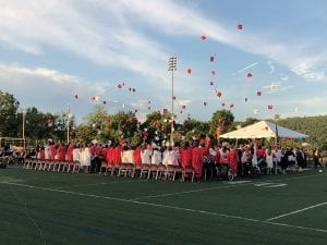 Graduates throwing red and white caps in the air
