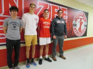 Three lacrosse players with coach in front of athletics wall poster