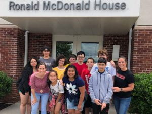 "Group of students and teachers under ""Ronald McDonald House"" sign"