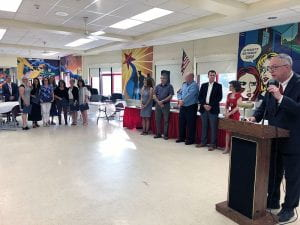 Staff, administrators standing with superintendent at podium