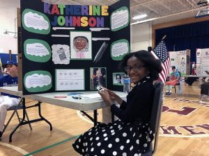 Student dressed as Katherine Johnson with trifold presentation board
