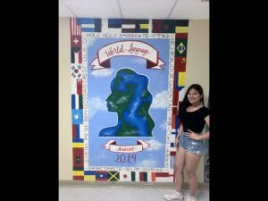 Female student standing next to world cultures wall mural