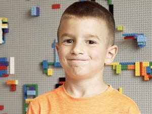 Smiling boy in orange shirt with Lego wall background