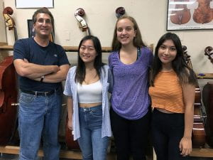 Teacher with three girls in music room